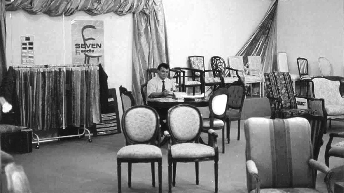 Diego Piva at an Italian furniture trade-fair, surrounded by his classic hand-made chairs
