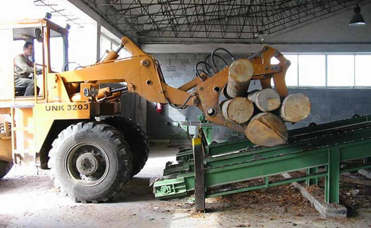 bulldozer transporting wood logs used to manufacture furniture at Sevensedie in Italy