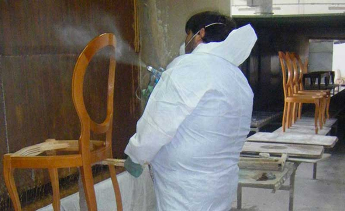 An operator polishing with a spray gun the structure of a classic wooden chair at Sevensedie in Italy