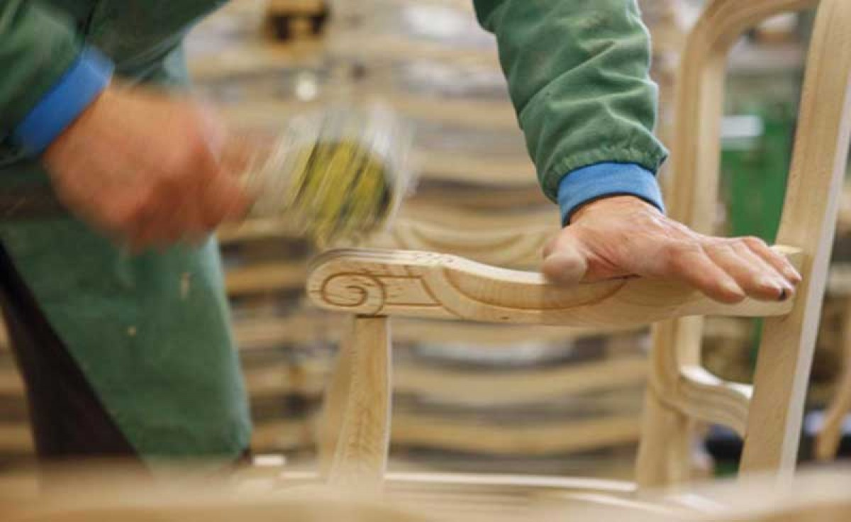 Operator assembling the armrest of a wooden chair at Sevensedie in Italy
