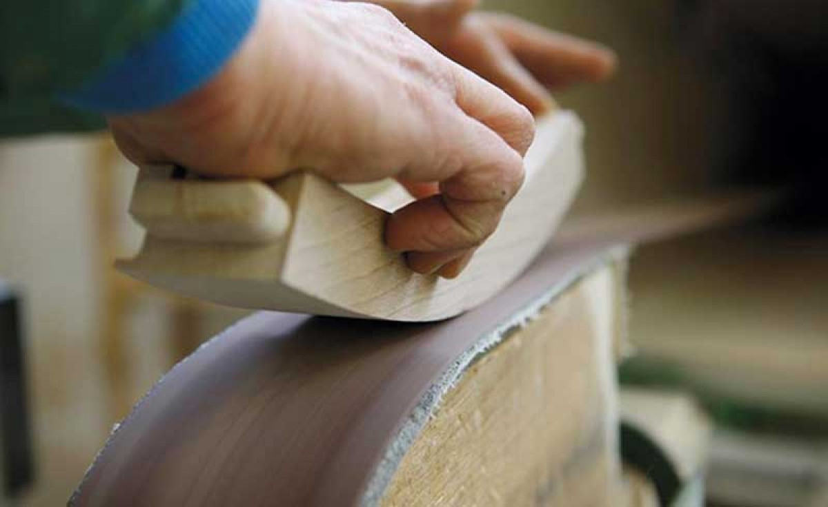 Italian manufacturer sanding the seat side rail of a wooden chair at Sevensedie