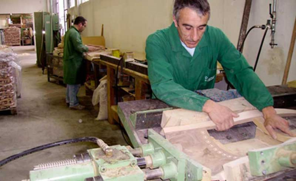 An operator assembling the backrest of a wooden classic chair at Sevensedie in Italy