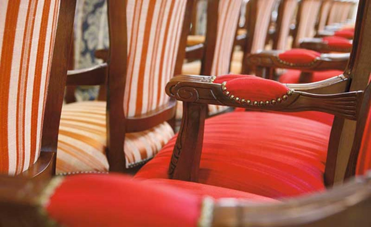 Row of classic chairs with wooden frame and red fabric