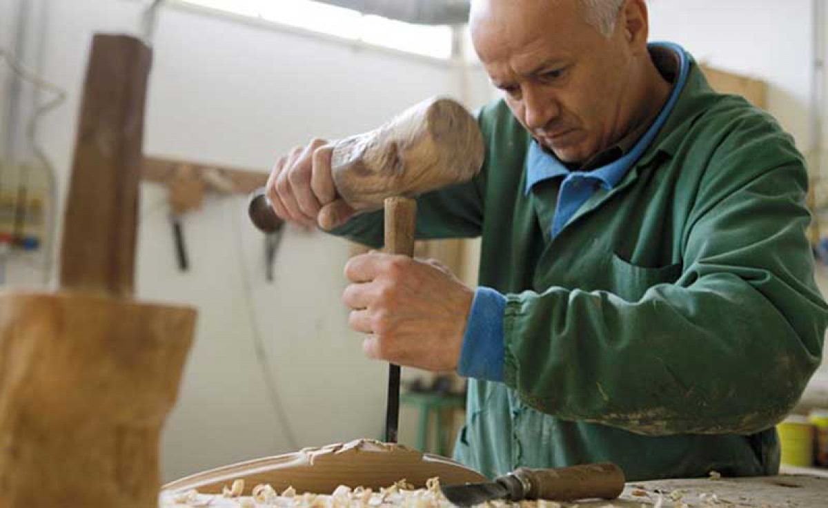 Operator hand-carves a chair at Sevensedie in Italy
