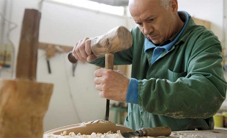 A Craftsman carving a chair at Sevensedie in Italy