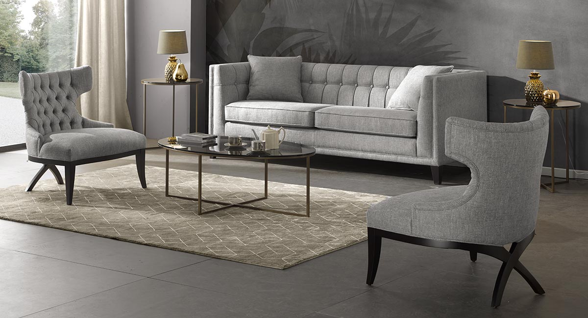 Contemporary Italian living room featuring a 3 seater sofa in a light blue bouchl� fabric with matching color chairs. In front of the sofa an elegant oval coffee table with metal base and smoked glass top