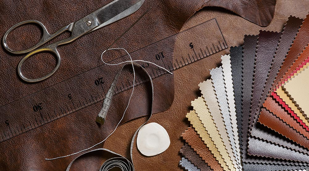 Several leather hides in different colors in rolls, brown , black grey, light brown and blue
