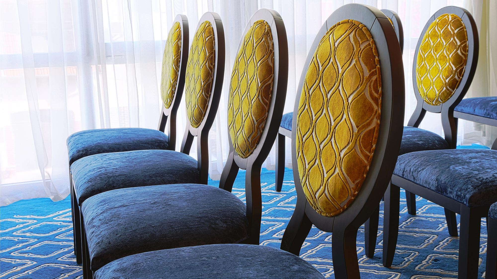 Close picture showing the details of a few Anello chairs upholstered in a two tone blue and yellow velvet. Hi quality contemporary dining chairs, 100% made in Italy