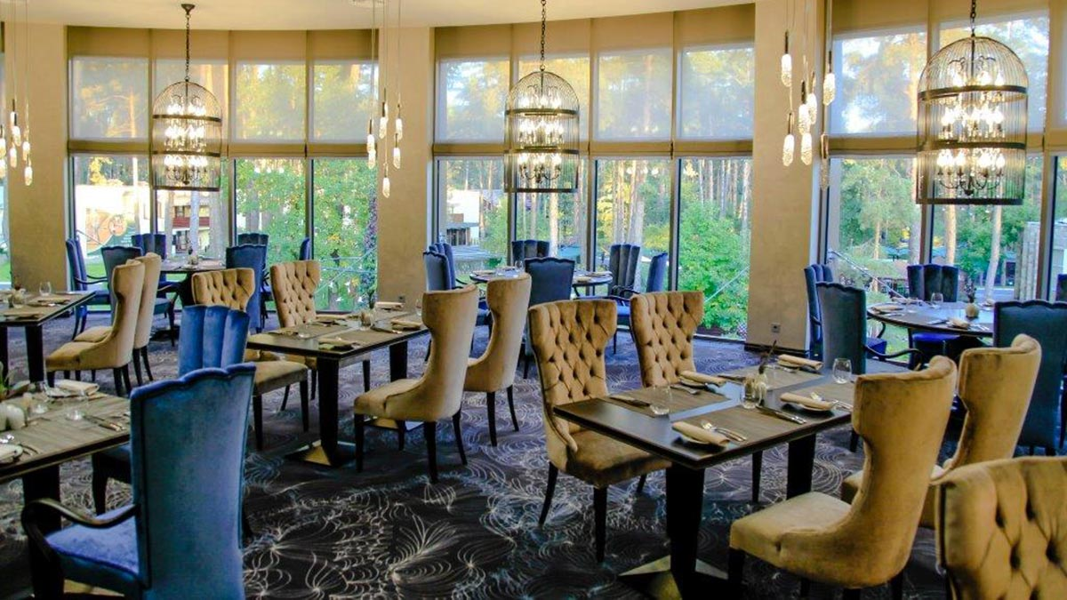 general view of the dining area of the Mozart restaurant looking out into the forest. 10 contemporary high back Queen dining chair, 10 square Atene dining tables ad a few large Bisotus round table. Hi quality Italian furniture by Sevensedie, 100% made in Italy
